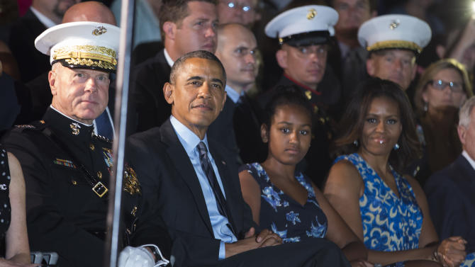 From left, Marine Commandant Gen. James Amos, President Barack Obama, Sasha Obama, and first lady Michelle Obama look on during the Marine Barracks Evening Parade, on Friday, June 27, 2014, in Washington. (AP Photo/ Evan Vucci)