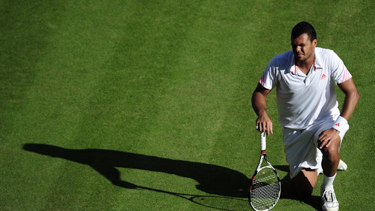 Jo-Wilfried Tsonga of France kneels on the court after being hit by a ball during a men's semifinals match against Andy Murray of Britain at the All England Lawn Tennis Championships at Wimbledon, England, Friday, July 6, 2012. (AP Photo/Adam Davy, Pool)