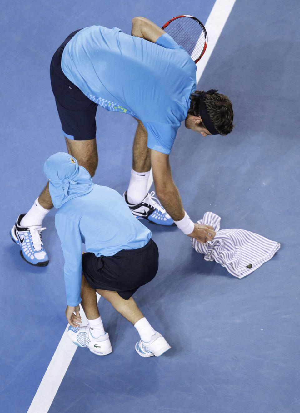 Argentina's Juan Martin Del Potro collects bugs off the court wiuth the help of a ball boy during his third round match against Taiwan's Lu Yen-Hsen at the Australian Open tennis championship, in Melbourne, Australia, Friday, Jan. 20, 2012. (AP Photo/Sarah Ivey)