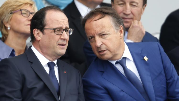 French President Francois Hollande and France's Senate Speaker Jean-Pierre Bel attend the traditional Bastille Day parade on the Place de la Concorde in Paris
