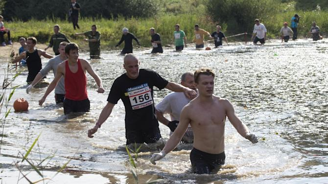 "Men walk in a lake as they take part in a ""Brave Run"" competition in Minsk"