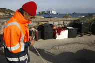 A fisherman adjusts a net as the grounded cruise ship Costa Concordia is seen in background, off the Tuscan island of Giglio, Italy, Sunday, Jan. 22, 2012. Rescuers on Sunday resumed searching the above-water section of the capsized Costa Concordia cruise liner, but choppy seas kept divers from exploring the submerged part, where officials have said there could be bodies. Civil protection officials said that until the waves slack off, divers would not swim into the submerged part of the vessel just off the port of Giglio, a tiny Island off the Tuscan coast. (AP Photo/Pier Paolo Cito)