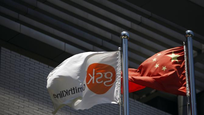 File picture shows a flag bearing the logo of GlaxoSmithKline fluttering next to a Chinese national flag outside a GlaxoSmithKline office building in Shanghai
