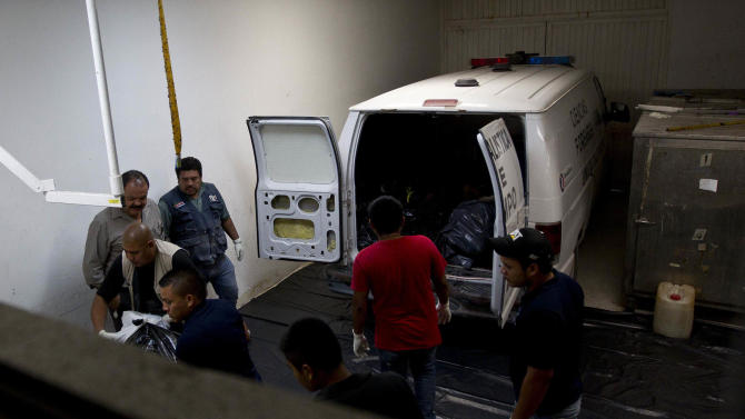 Morgue employees remove the bodies of people who were killed by an explosion at a gas pipeline distribution center in Reynosa, Mexico, near Mexico's border with the U.S., Tuesday Sept. 18, 2012.  Mexico's state-owned oil company says at least five people are still listed as missing in a pipeline fire that killed over 20 workers and injured over 40 others on Tuesday. (AP Photo/Hans-Maximo Musielik)