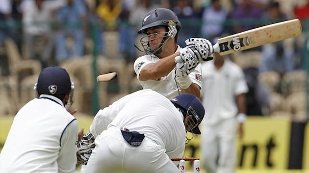 A protective guard flies off the arm of New Zealand's captain Ross Taylor (rear) as he hits a shot during the first day of their second test cricket match against India in Bangalore (Reuters)