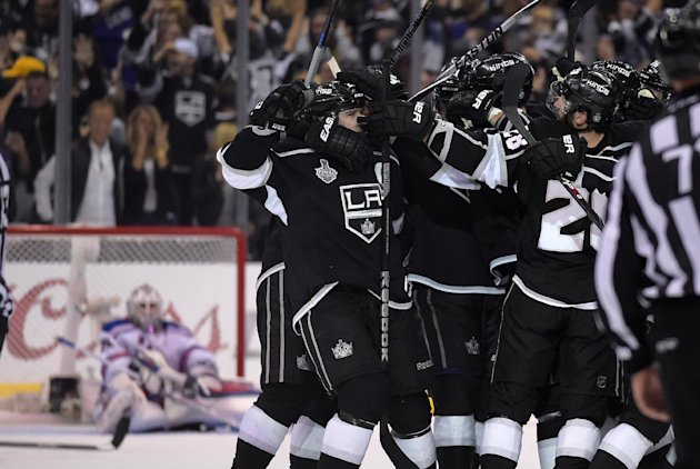 Members on the Los Angeles Kings, right, celebrates a game-winning goal by right wing Dustin Brown as New York Rangers goalie Henrik Lundqvist, left, ...