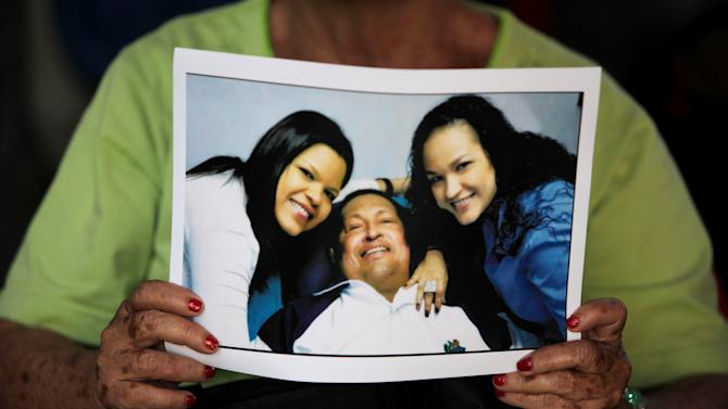 A man holds a print of one of the photographs released Friday by the government showing President Hugo Chavez with his daughters Maria Gabriela, left, and Rosa Virginia, right, at Bolivar square in Caracas, Venezuela, Friday, Feb. 15, 2013.   Amid widespread speculation and rumors in Venezuela about Chavez's delicate condition following his Dec. 11 cancer surgery, the government released the first photos of the ailing president in more than two months on Friday, presenting images of him smiling alongside his daughters in Cuba. (AP Photo/Fernando Llano)