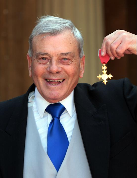 Former British cricket umpire Harold (Dickie) Bird poses for pictures after receiving the Officer of the British Empire, (OBE) which was presented to him by Prince Charles at Buckingham Palace in Lond