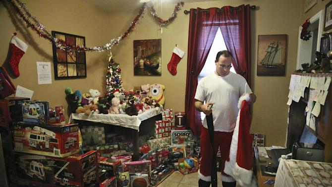 In this photo taken Tuesday, Dec. 18, 2012, Michael Sciaraffo, a political consultant who has worked for Hillary Clinton and City Hall, is surrounded by donated toys as he prepares his Santa Claus costume, in the Brooklyn borough of New York.  Using Facebook, Sciaraffo started a charitable enterprise to collect and personally deliver toys to children affected by Superstorm Sandy victims dressed as Santa Claus.  (AP Photo/Bebeto Matthews)