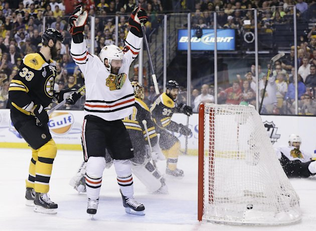 Chicago Blackhawks left wing Brandon Saad, center, celebrates a goal by Chicago Blackhawks center Michal Handzus, right, of Slovakia, in front of Boston Bruins defenseman Zdeno Chara (33), of Slovakia