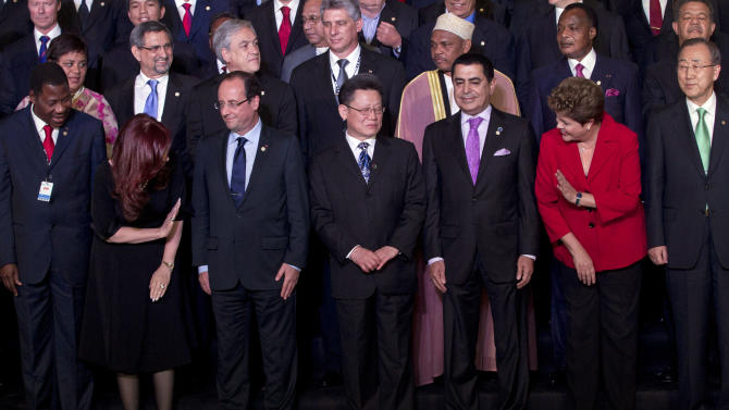 Argentina's President Cristina Fernandez, second from left, waves to Brazil's President Dilma Rousseff, second from right, during the group photo at the United Nations Conference on Sustainable Development, or Rio+20, in Rio de Janeiro, Brazil, Wednesday, June 20, 2012. Also in the picture are France's President Francois Hollande, front row third from left, and United Nations Secretary General Ban Ki-Moon, front row right. (AP Photo/Victor R. Caivano)