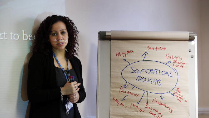In this Feb. 5, 2013 photo, psychological well-being practitioner Nabila El-Zanaty talks to a self-help psychological course class run by Britain's publicly funded health system, during a session in east London. With a long wait to see a psychologist, the British government is turning to the classroom to treat people with mild to moderate mental health problems with a mix of PowerPoint presentations and group exercises. While some dismiss the approach as do-it-yourself therapy, experts say there is convincing evidence that people with conditions like depression and anxiety can be successfully treated without ever seeing a psychologist or a psychiatrist. (AP Photo/Lefteris Pitarakis)