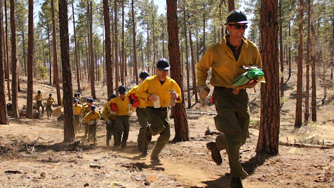 In this 2012 photo provided by the Cronkite News, members of the Granite Mountain Hotshots run during training on the use of emergency fire shelters. On Sunday, June 30, 2013, 19 members of the Prescott, Ariz.-based crew were killed in the deadliest wildfire involving firefighters in the U.S. for at least 30 years. The firefighters were forced to deploy their emergency fire shelters - tent-like structures meant to shield firefighters from flames and heat - when they were caught near the central Arizona town of Yarnell, according to a state forestry spokesman. (AP Photo/Cronkite News, Connor Radnovich)