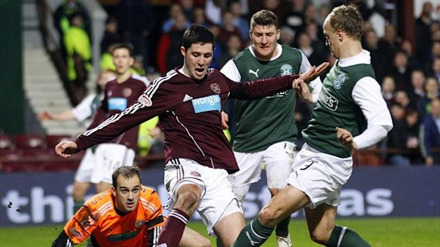 Hibernian's Leigh Griffiths(R) has his shot at the empty Hearts' goal blocked by Dylan McGowan during their Scottish Premier League match at Tynecastle