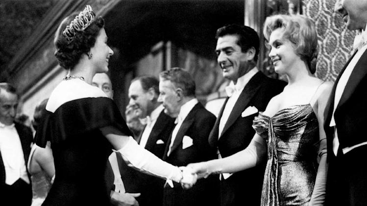 "In this late October 1956 photo provided by courtesy Running Press, Marilyn Monroe, right,  wearing a burnished gold lamé gown meets Queen Elizabeth in London. The photograph is included in a new 2012 book, ""Marilyn in Fashion,"" published by Running Press. Monroe passed away a half-century ago this week, a murky death that remains one of Hollywood's most tantalizing mysteries. But look around: Her legend lives on, more vibrantly than ever. In a twist she surely would have appreciated, this 1950's bombshell has become a 21st-century pop culture phenom. (AP Photo/Courtesy Running Press)"