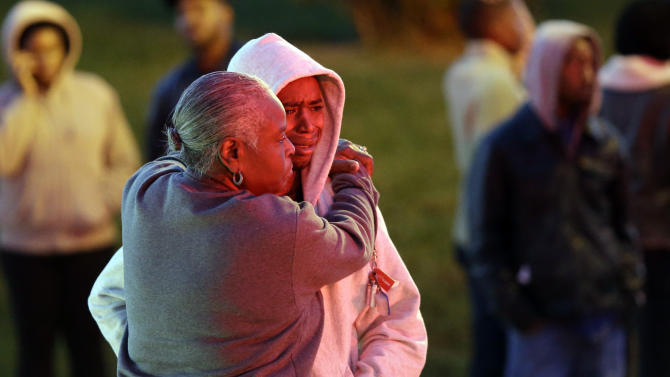Barbara Hopkins, left, hugs her grandson, whose nickname was only given as Mick, outside of Hopkin's son's house in Baltimore, Thursday, Oct. 11, 2012, where an early morning fire claimed the lives of an adult and four children. (AP Photo/Patrick Semansky)