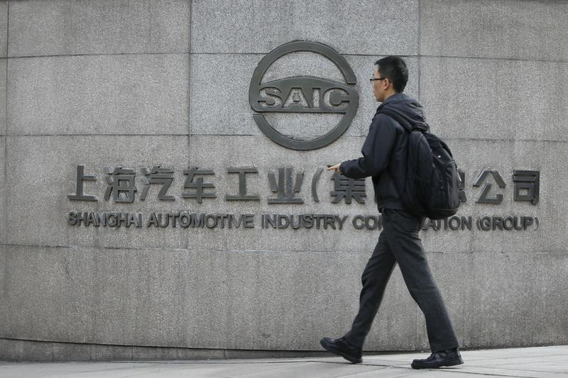 A man walks in front of the gate of Shanghai Automotive Industry Corp., in Shanghai