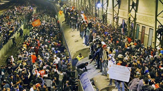 """FILE - In this Thursday, Feb. 2, 2012 file photo, Egyptians crowd a train station waiting for their friends and relatives' arrival from Port Said in Cairo, Egypt. More Arabs are politically engaged than ever before, demanding to be heard. They're learning what it means to question everything and everyone after decades under heavy autocracies where discussion, innovation and public participation were discouraged or crushed. This week, as Egyptians prepare to mark on Friday the anniversary of the start of the revolution that swept aside Hosni Mubarak, the issue seems to come up at every panel that even tangentially touches on politics or strategy. A man, right, carries a poster with Arabic that reads, """"rest in peace, who's behind this? we are with those who lost their relatives."""" (AP Photo)"""