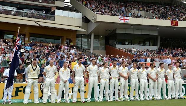 Australian cricketers observe a minutes silence to mark the passing of former South African president Nelson Mandela, on the second day of their second Ashes Test match against England, in Adelaide, o