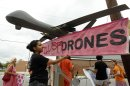 "A demonstrator adjusts a sign reading ""Stop Killer Drones"" hung on a mock drone at the gates of Fort McNair where President Barack Obama will speak at the National Defense University in Washington"