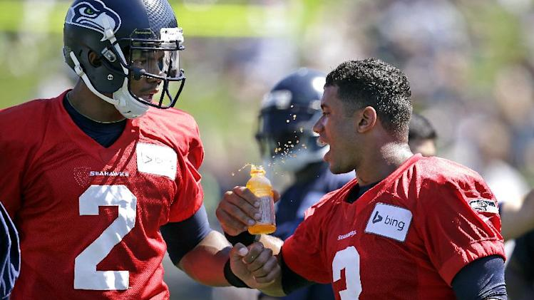 Seattle Seahawks quarterback Terrelle Pryor (2) teases fellow quarterback Russell Wilson by bumping his drink while walking past at an NFL football camp practice on Saturday, July 26, 2014, in Renton, Wash