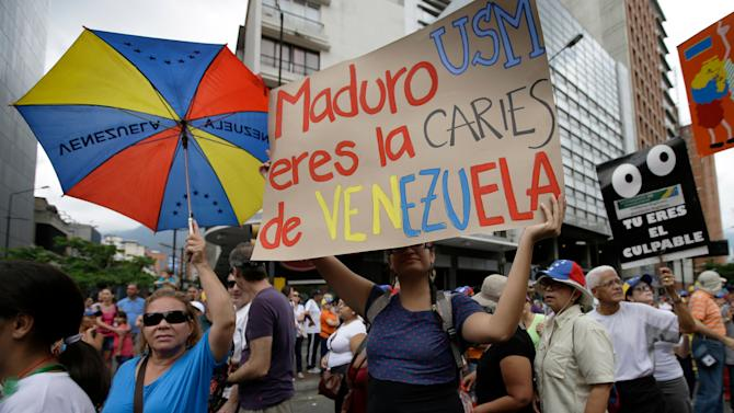 """An opposition protester holds up a poster that reads in Spanish """"Maduro you are the cavity of Venezuela"""" during an opposition May Day march in Caracas, Venezuela, Wednesday, May 1, 2013.  Venezuelans filled the streets of the capital Wednesday in rival marches by the opposition and the government less than a day after a brawl on the floor of congress injured several opposition lawmakers. (AP Photo/Fernando Llano)"""