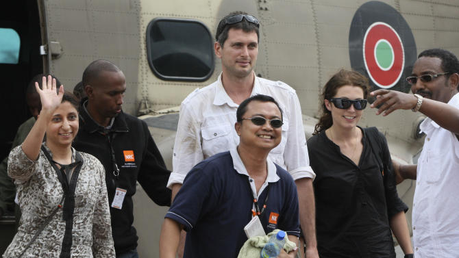 Released aid workers Qurat-Ul-Ain Sadazai, 38, a Canadian citizen of Pakistani origin, left, Glenn Costes of the Philippines, 40, center, Steven Dennis of Canada, 37, above-center, and Astrid Sehl of Norway, 33, center-right, arrive back by Kenyan military helicopter at Wilson airport in Nairobi, Kenya Monday, July 2, 2012. A pro-government Somali militia group said Monday that it rescued the four aid workers kidnapped by gunmen from a refugee camp in Kenya last week. (AP Photo/Sayyid Azim)