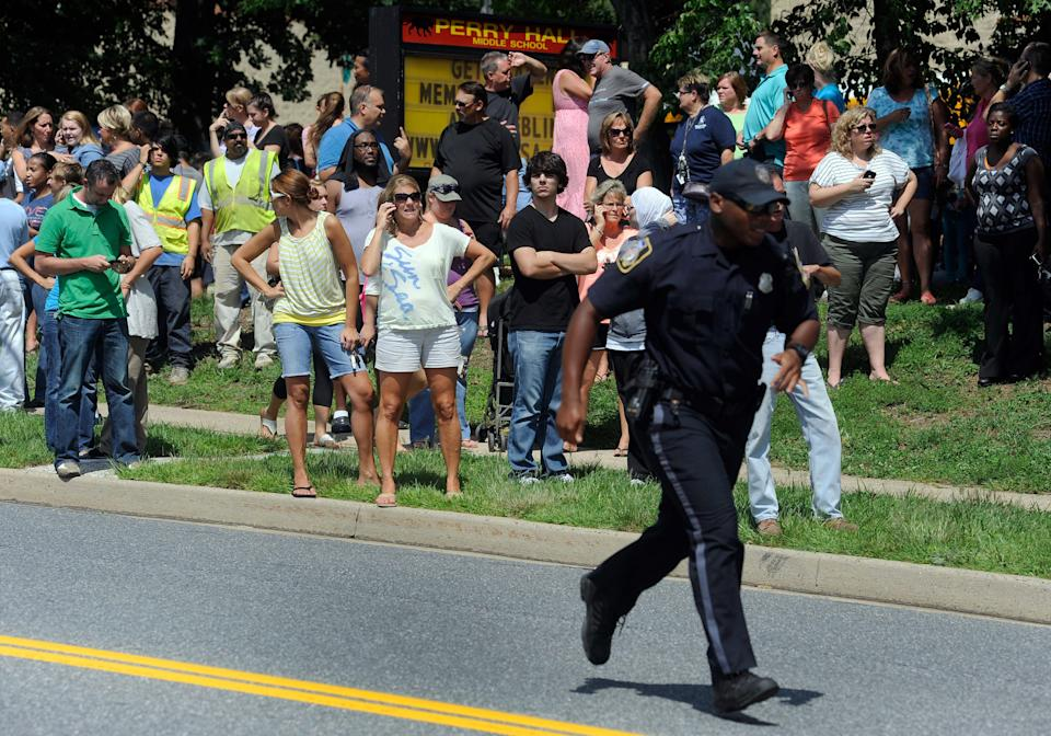 Parents wait to reunite with their children after a student was shot and critically wounded on the first day of classes at Perry Hall High School, Monday, Aug. 27, 2012, in Perry Hall, Md. A suspect was taken into custody shortly after the shooting, according to police. No one else was reported injured. (AP Photo/Steve Ruark)