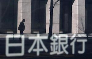 A man walking past a building is reflected in a sign board of the Bank of Japan building in Tokyo