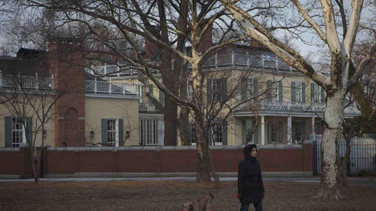 A woman and a dog walk past Gracie Mansion in New York
