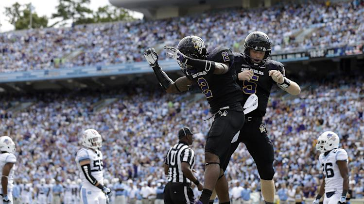 In this Sept. 28, 2013, file photo, East Carolina quarterback Shane Carden (5) and Justin Hardy (2) celebrate Carden's touchdown against North Carolina during the first half of an NCAA college football game in Chapel Hill, N.C.  Hardy started his East Carolina career as a walk-on catching passes from Carden on the scout team. The two are still doing it four years later, only now Hardy has a chance to become the all-time catches leader in FBS history