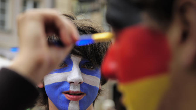 A soccer fan, face painted with the colors of Greece's national flag, watches another having his face painted with the german national flag colors before the Euro 2012 soccer championship quarterfinal match between Germany and Greece in Gdansk, Poland, Friday, June 22, 2012. (AP Photo/Alvaro Barrientos)
