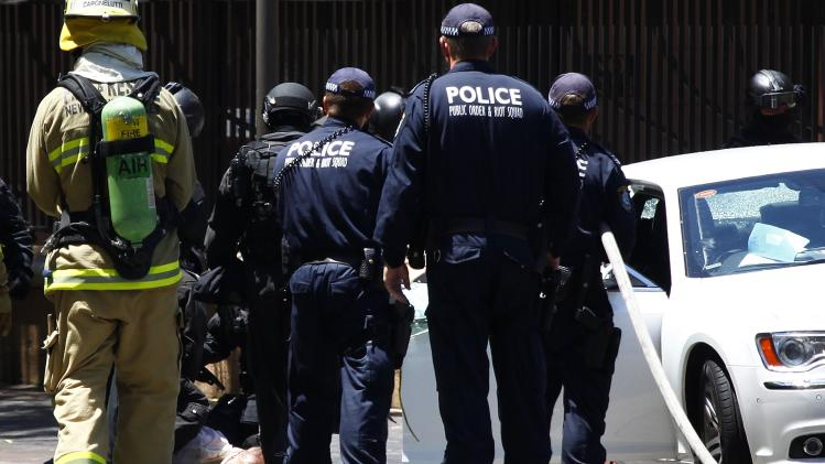 Heavily armed police officers drag a man out of a car outside the New South Wales state parliament building in Sydney