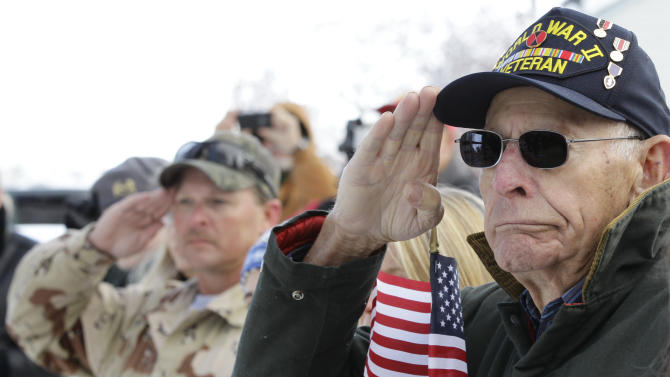 World War II combat veteran Ben Kauffman, age 86, carries an American flag as he listens to a speaker during a Veterans Day ceremony in the small town of Loveland, Colo., Sunday Nov. 11, 2012. Kauffman, who fought in the Battle of Okinawa in 1945 with the U.S. Army's 17th Infantry Regiment, also served in Korea. (AP Photo/Brennan Linsley)