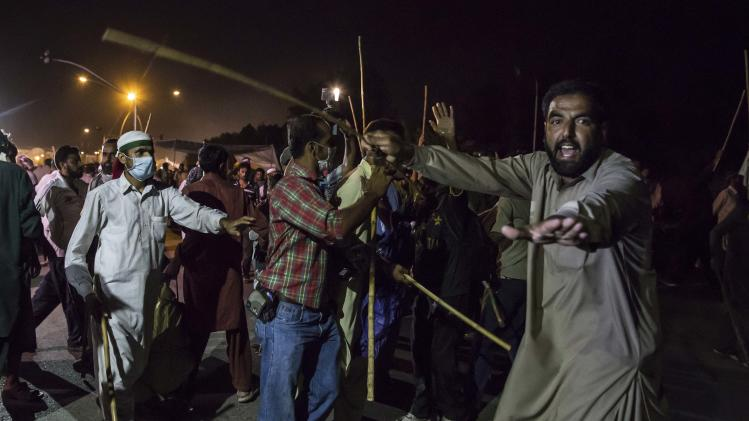 A supporter of Tahir ul-Qadri tries to stop fellow supporters from attacking riot police in Islamabad