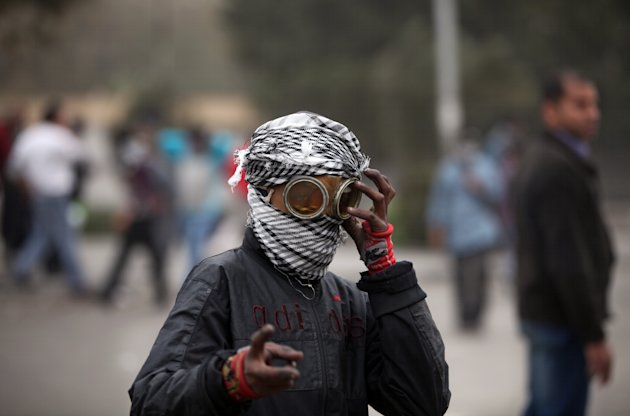 An Egyptian protester covers his face during clashes with riot police, not seen, near Tahrir Square, Cairo, Egypt, Monday, Jan. 28, 2013. Health and security officials say a protester has been killed