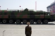 A North Korean soldier stands guard in front of a military vehicle carrying what is believed to be a Taepodong-class missile during a military parade in Pyongyang in April 2012. North Korea plans to launch a long-range rocket between December 10 and 22, the North's official news agency said Saturday