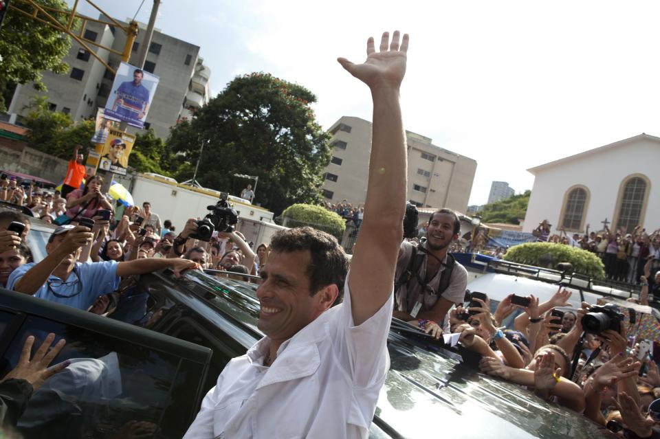 Opposition presidential candidate Henrique Capriles waves to supporters as he leaves a polling station after voting in the presidential election in Caracas, Venezuela, Sunday, Oct. 7, 2012. Capriles is running against President Hugo Chavez. (AP Photo/Ramon Espinosa)