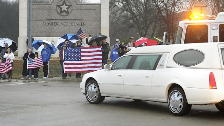 Mourners hold U.S. flags as a hearse containing Chris Kyle's casket leads a motorcade leaving the Multi-Purpose Stadium, in Midlothian, Texas, Tuesday, Feb. 12, 2013 for the 200-mile journey to Austin, where Kyle will be buried at the Texas State Cemetery. Some 7,000 people attended a two-hour memorial service for Kyle at Cowboys Stadium in Arlington on Monday. Kyle and his friend Chad Littlefield were shot and killed Feb 2. at a North Texas gun range. (AP Photo/Star-Telegram, Max Faulkner)