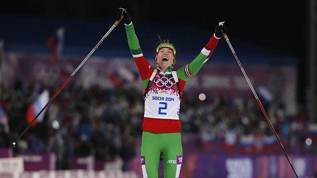Darya Domracheva of Belarus celebrates as she approaches the finish line to win the women's biathlon 12.5km mass start event (Reuters)