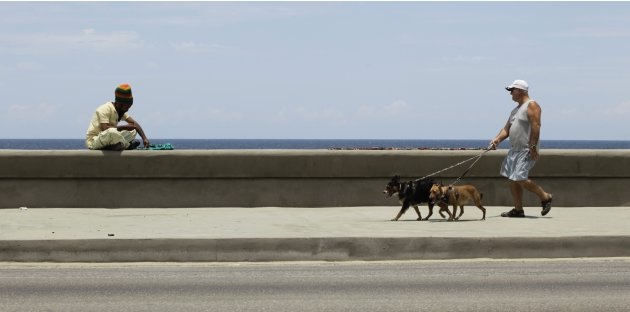 A man makes necklaces to sell as another walks his dogs on Havana's seafront boulevard 'El Malecon'