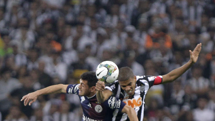 Lautaro Acosta of Argentina's Lanus, left, fights for the ball against Leornado SIlva of Brazil's Atletico Mineiro during the Recopa Sudamericana final match in Belo Horizonte, Brazil, Wednesday, July 23, 2014. (AP Photo/Bruno Magalhaes)