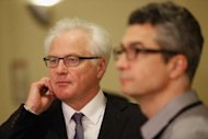 Russian Ambassador to the United Nations Vitaly Churkin (L) waits to speak to the media after a UN Security Council meeting on Syria. The Security Council held discussions following a massacre of more than 100 civilians in Houla