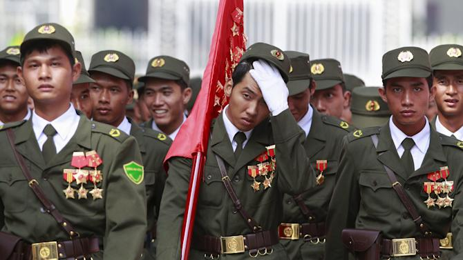 Vietnamese village policemen walk in front of the Unification Palace (formerly Presidential Palace) after a rehearsal for a military parade as part of the 40th anniversary of the fall of Saigon in southern Ho Chi Minh City (formerly Saigon City), Vietnam
