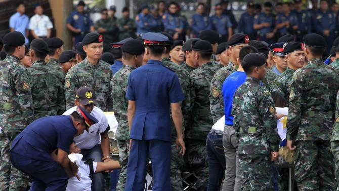 A woman reacts after viewing a metal casket containing the body of her relative, who was killed in Sunday's clash with Muslim rebels, at Villamor Air Base in Pasay city