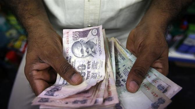 File photo of a private money trader counting Indian rupee currency notes at a shop in Mumbai