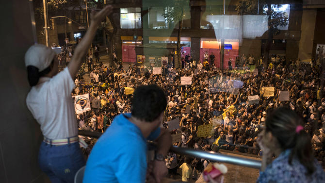 People eating at a restaurant observe as demonstrators march toward the Cinelandia square during a protest in Rio de Janeiro, Brazil, Monday, June 24, 2013. Under pressure after more than a week of nationwide protests, Brazilian leader Dilma Rousseff said Monday her government will spend $23 billion more on public transportation and announced five core areas that leaders will focus on to speed political reform and improvements to government services. Rousseff made the announcement after meeting with leaders of a free-transit activist group that launched the first demonstrations more than a week ago and has called for new protests Tuesday.(AP Photo/Felipe Dana)