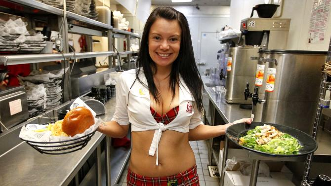 "In this May 16, 2012 photo, Valerie Chaira carries lunch from the kitchen at the Tilted Kilt, in Tempe, Ariz. The Tilted Kilt is part of a booming niche in the beleaguered restaurant industry known as ""breastaurants,"" or sports bars that feature scantily-clad waitresses. These small chains operate in the tradition of Hooters, which pioneered the concept in the 1980s but has struggled in recent years to stay fresh. (AP Photo/Matt York)"