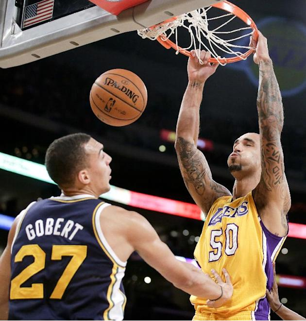 Los Angeles Lakers center Robert Sacre, right, dunks ovre Utah Jazz center Rudy Gobert during the second half of a preseason NBA basketball game in Los Angeles, Tuesday, Oct. 22, 2013