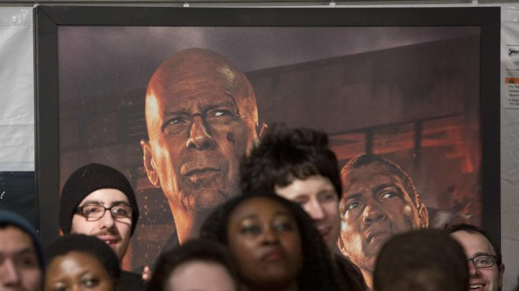 "A poster featuring cast members Bruce Willis and Jai Courtney hangs behind a crowd as the actors met with fans to celebrate the opening of their new film ""A Good Day To Die Hard"" in New York"